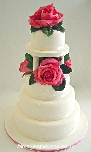 Ivory Wedding Cake. Stacked with Pillars and large Roses