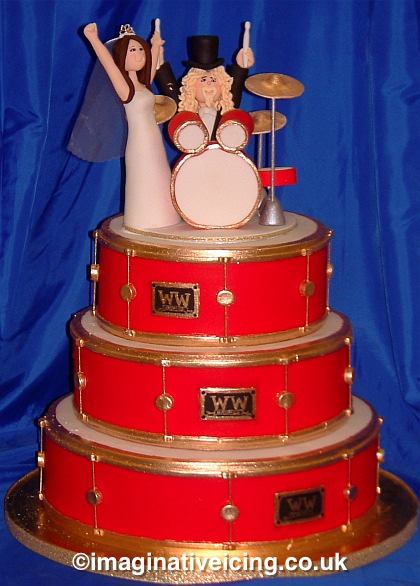 Wedding Cake with 3 tiers shaped like drums stacked together with Icing bride & groom models playing a icing drum kit cake topper