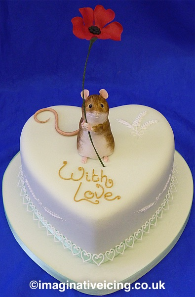 Icing Field mouse with red handmade sugar flower on top of a pale green heart cake with piped lace