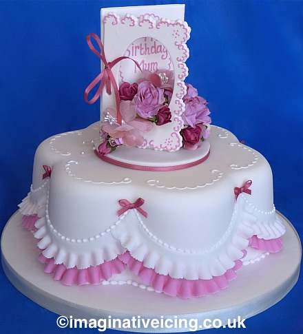 """Happy Birthday Mum"" - Edible Icing Birthday Card cake topper with silk flowers and piped inscription, on top of a petal shaped cake with pretty pink and white icing frills."