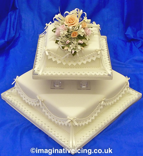 Square Ivory Wedding Cake With Delicately Coloured Sugar Flowers Lace Effect Frills Satin Bows