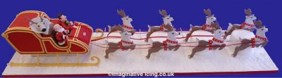 Arthur Christmas Cake Sleigh with gingerbread reigndeer resting against mini cakes