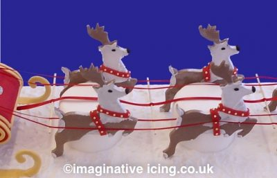 Close up of the gingerbread reindeer - Arthur Christmas Cake Sleigh with gingerbread reindeer resting against mini cakes